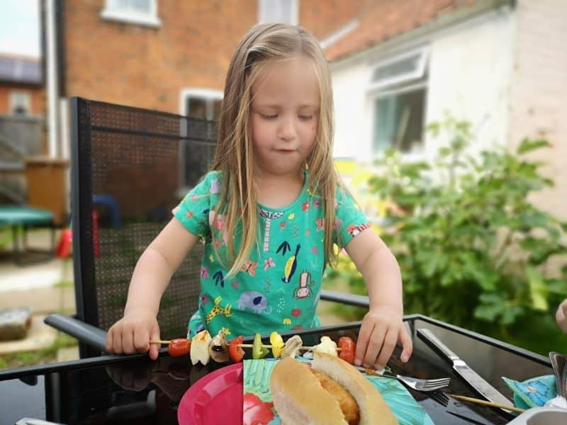 Erin eating a vegetable skewer