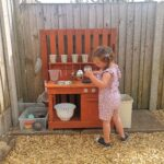 Erin enjoying the mud kitchen