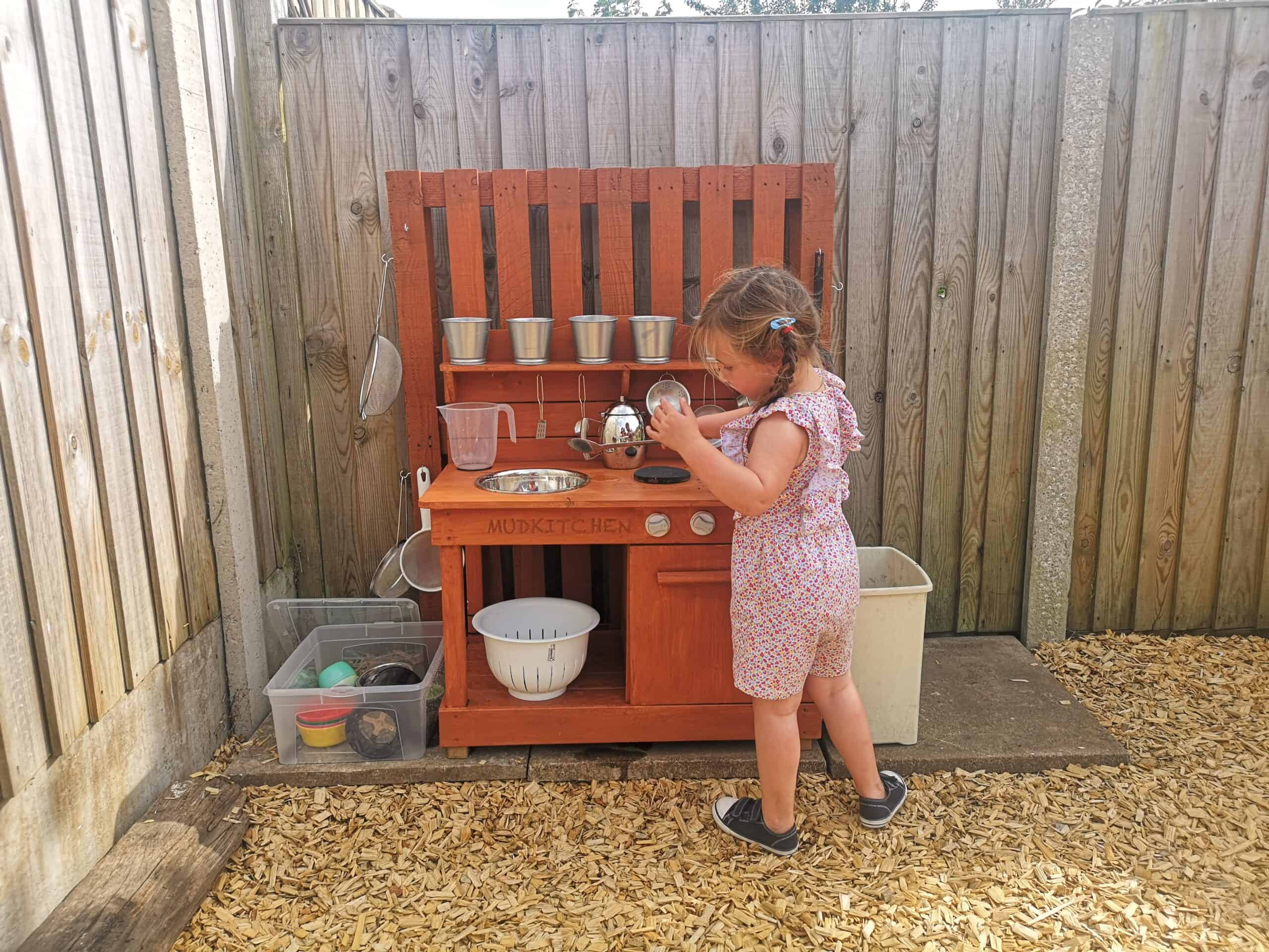 Erin enjoying the mud kitchen
