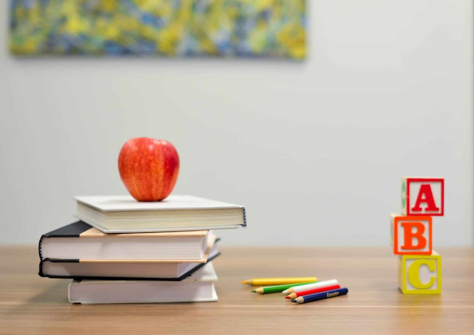Books with an apple on a desk