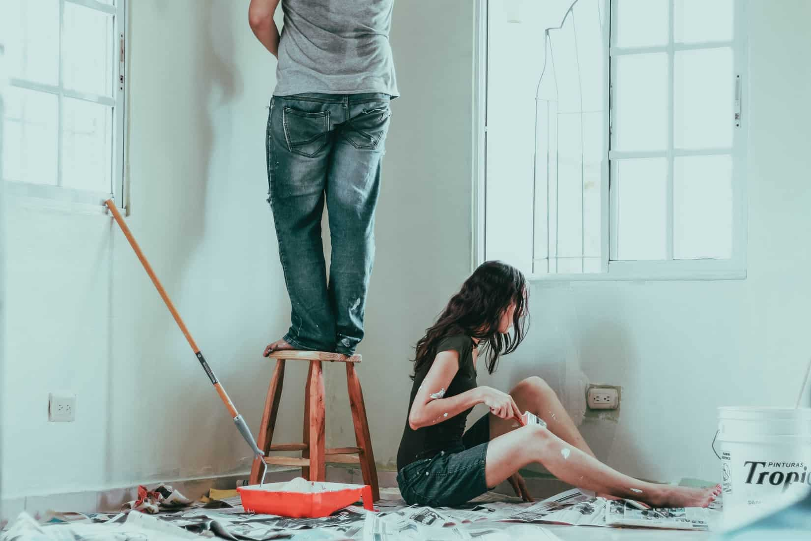 Man and woman decorating a room