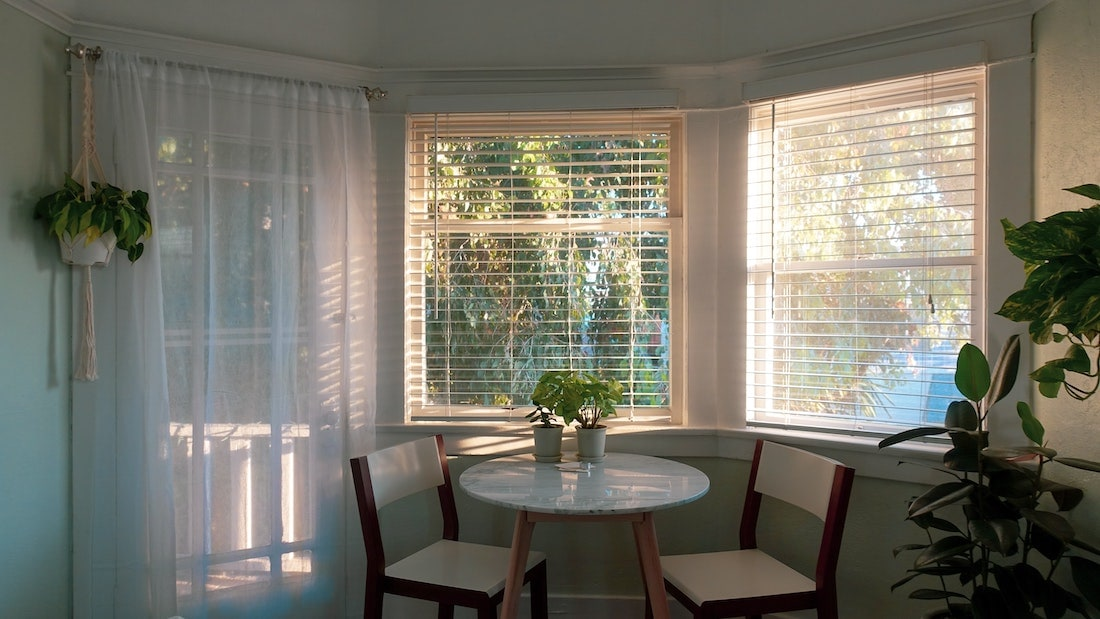 Large room with blinds and sheer curtains on the windows