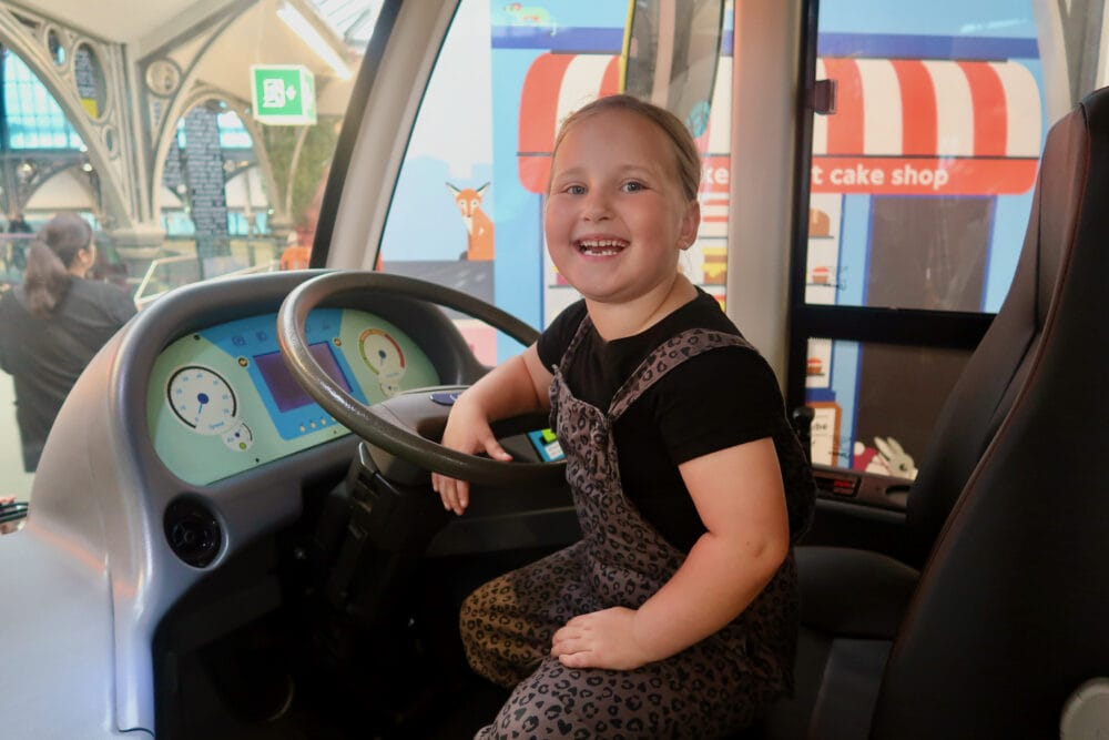 Erin driving a London bus at London Transport Museum