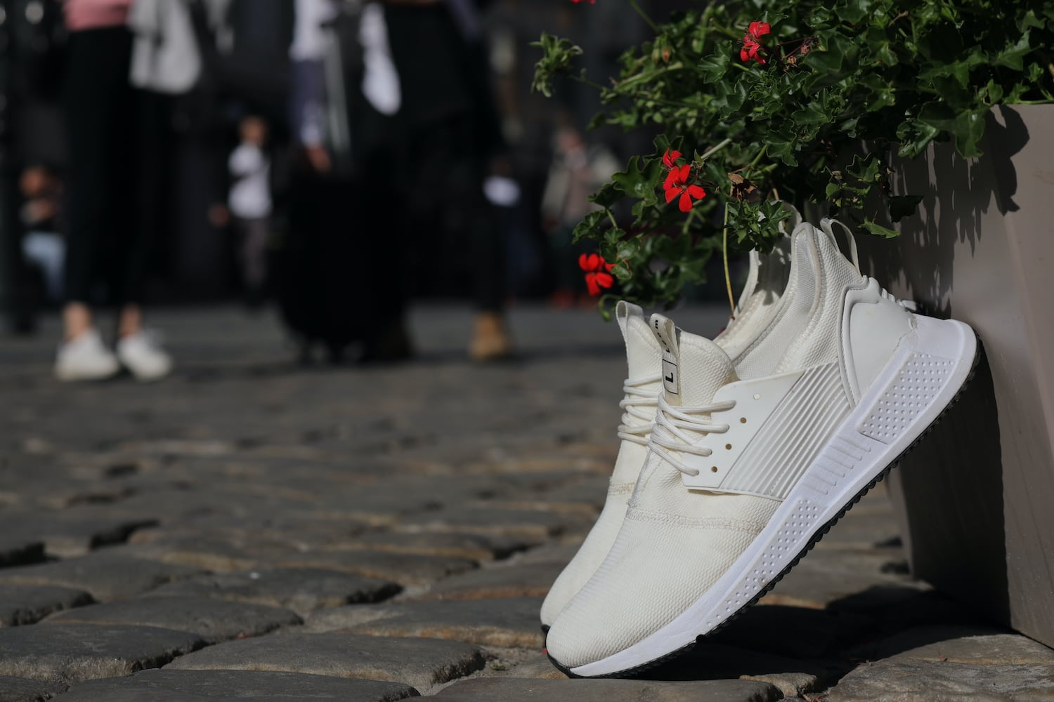 Loom white trainers propped up
