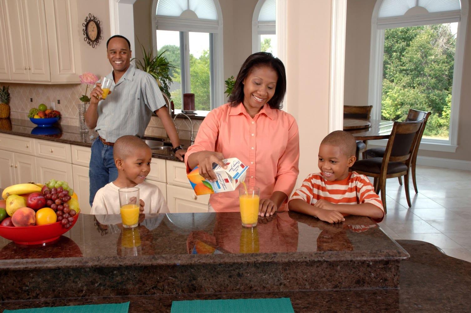 Family around a breakfast bar pouring orange juice