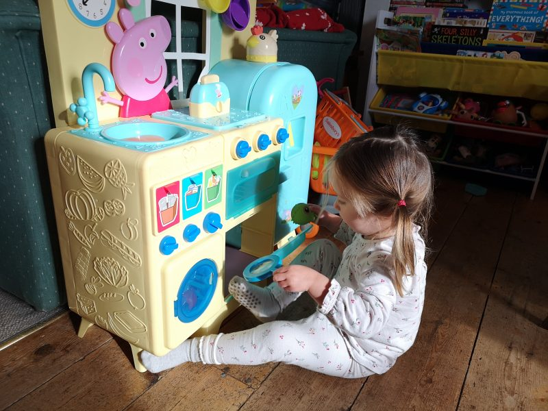 Erin playing with the Peppa Pig kitchen